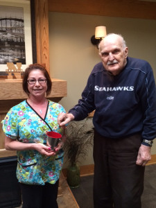 Joseph Krause, resident council president at Seneca Health Care Center drops a penny into the collection cup for the Pennies from Heaven campaign that was started by Margarita Merced of West Seneca three years ago.